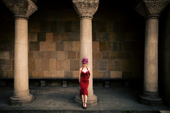 Elegant woman with cylinder. Young elegant woman in red dress and cylinder   against column, full body shot Stock Photo