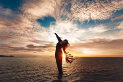Elegant woman dancing on water. Sunset and silhouette. Royalty Free Stock Images