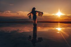 Elegant woman dancing on water. Sunset and silhouette Stock Image