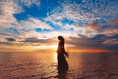 Elegant woman dancing on water. Sunset and silhouette Royalty Free Stock Photo