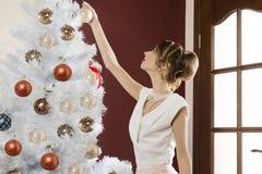 Elegant woman decorating xmas tree Stock Images