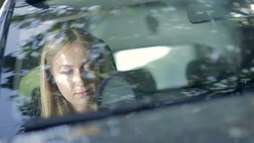 Elegant woman doing makeup in the car stock footage