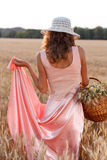Elegant woman in a dress and hat with basket Stock Image