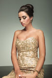 Elegant woman in dress sitting and looking sad Royalty Free Stock Photo