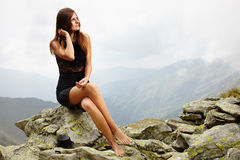 Elegant woman in dress sitting on the rocks Royalty Free Stock Photography
