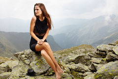 Elegant woman in dress sitting on the rocks Stock Images