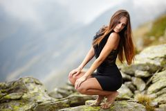 Elegant woman in dress sitting on the rocks Royalty Free Stock Photos