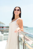 An elegant woman in a dress on a sky background. An attractive lady standing on a hotel balcony. A happy female in a sunglasses. Stock Image