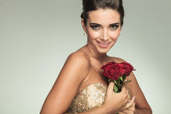 Elegant woman in dress smiling while holding red roses Stock Photos