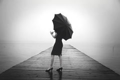 Elegant woman dressed in black hiding with umbrella Royalty Free Stock Photos