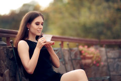 Elegant Woman Drinking a Coffee in the Garden Royalty Free Stock Image