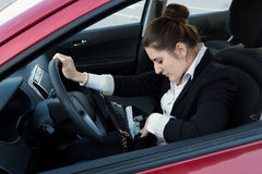 Elegant woman driving car and looking inside handbag Stock Photography