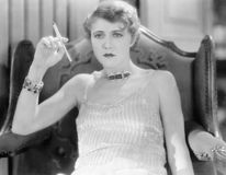 Elegant woman in an evening dress and jewelry smoking a cigarette Stock Image