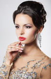 Elegant woman with evening hairstyle and earrings. Royalty Free Stock Images