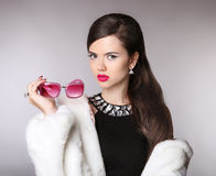 Elegant woman with fashion sunglasses, luxury jewelry, makeup, h Stock Image