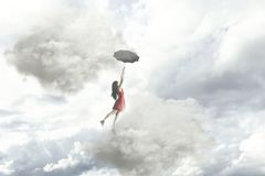 An elegant woman flying in the middle of the clouds hanging on her umbrella. Surreal moment of an elegant woman flying in the middle of the clouds hanging on her Stock Photo