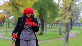 A woman unbuttons her coat in the autumn park. Elegant woman with glasses and a red umbrella unbuttons her coat in the autumn park stock footage