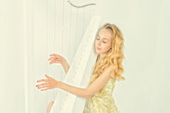 Elegant woman in gold dress with long blond hair playing the harp, on white background Stock Image