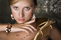 Elegant woman and gold jewelry Royalty Free Stock Images