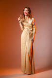 Elegant Woman in Golden Dress with wineglass Royalty Free Stock Photo