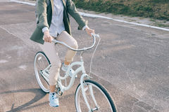 Elegant woman in a green shirt rides on the city bike on the roa Royalty Free Stock Image