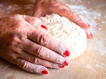 Elegant woman hands kneading and massaging homemade bread dough stock photography