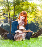Elegant woman has fun with her big dog in the park Stock Photo