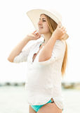 Elegant woman in hat standing on beach and looking at horizon Stock Image