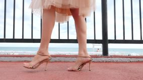 An elegant woman in a hat and a white air dress strolls along the waterfront. Legs close-up. 4k, slow-motion