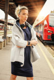 Elegant woman with headphones waiting a train at the railway sta Royalty Free Stock Photos