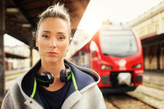 Elegant woman with headphones waiting a train at the railway sta Stock Photography