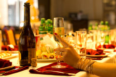 Elegant woman holding a flute of champagne. Hand of an elegant woman wearing gold bangles holding a flute of sparkling champagne resting on a dinner table set stock image