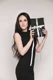 Elegant woman holding gift. Young beautiful woman with long hair wearing black cocktail dress is holding elegantly wrapped gift Stock Images