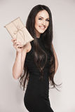Elegant woman holding gift. Young beautiful woman with long hair wearing black cocktail dress is holding elegantly wrapped gift Royalty Free Stock Photos