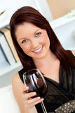 Elegant woman holding a glass of wine at home Royalty Free Stock Images