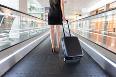 Elegant woman is holding her luggage on escalator Royalty Free Stock Photo
