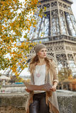 Elegant woman holding map and looking into the distance in Paris Royalty Free Stock Image