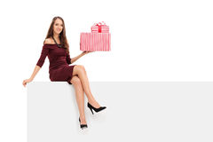 Elegant woman holding presents seated on panel Stock Images