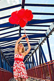 Elegant woman holding red balloons Stock Photography