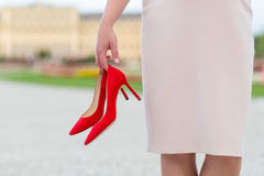 Elegant woman holding red high heels shoes in her hands Stock Photos