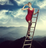 Elegant woman on a ladder Stock Images