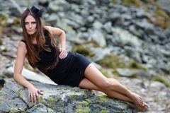 Elegant woman laying on the mountain rocks Stock Photo