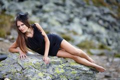 Elegant woman laying on the mountain rocks Stock Image
