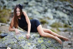 Elegant woman laying on the mountain rocks Royalty Free Stock Photos