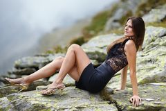 Elegant woman laying on the mountain rocks Royalty Free Stock Photo
