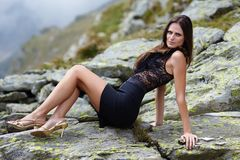 Elegant woman laying on the mountain rocks Royalty Free Stock Image