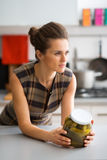 Elegant woman leaning on kitchen counter holding jar of pickles. An elegant woman leans on her kitchen counter, holding a jar of pickles, and looking off into Royalty Free Stock Photos