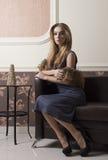 Elegant woman on leather sofa Stock Photo