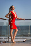 An elegant woman on a light sea background. A beautiful lady in a bright red dress with a cleavage. A girl posing on a terrace. Royalty Free Stock Photo