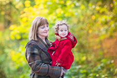 Elegant woman with little toddler girl in autumn park Royalty Free Stock Images